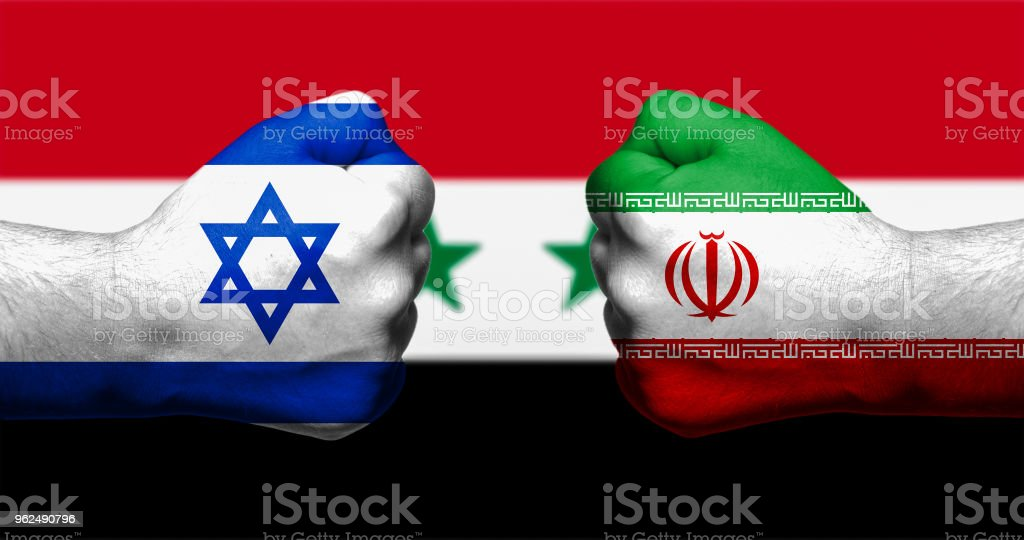 Flags of Israel and Iran painted on two clenched fists facing each other with flag of Syria in the background/Israel - Iran conflict concept - Royalty-free Agreement Stock Photo