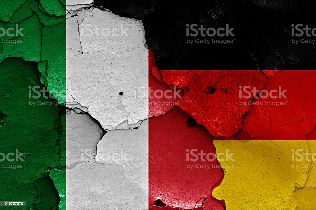 flags of Italy and Germany painted on cracked wall stock photo