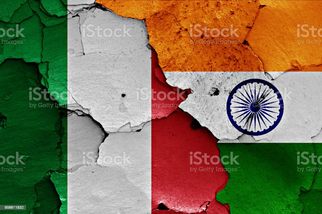 flags of Italy and India painted on cracked wall stock photo