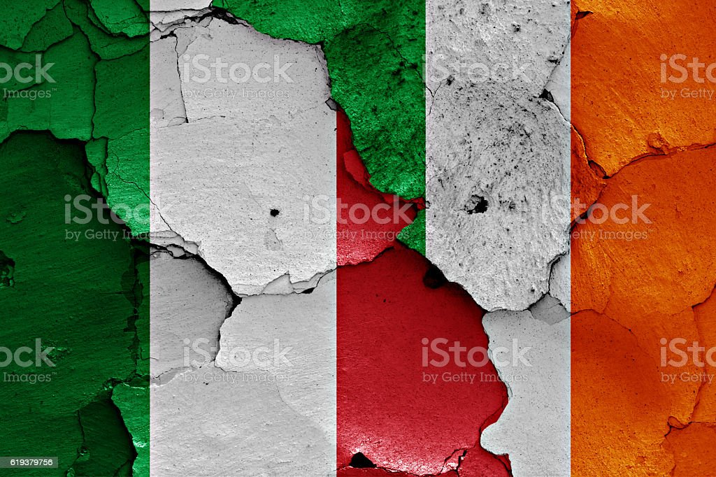 flags of Italy and Ireland painted on cracked wall stock photo