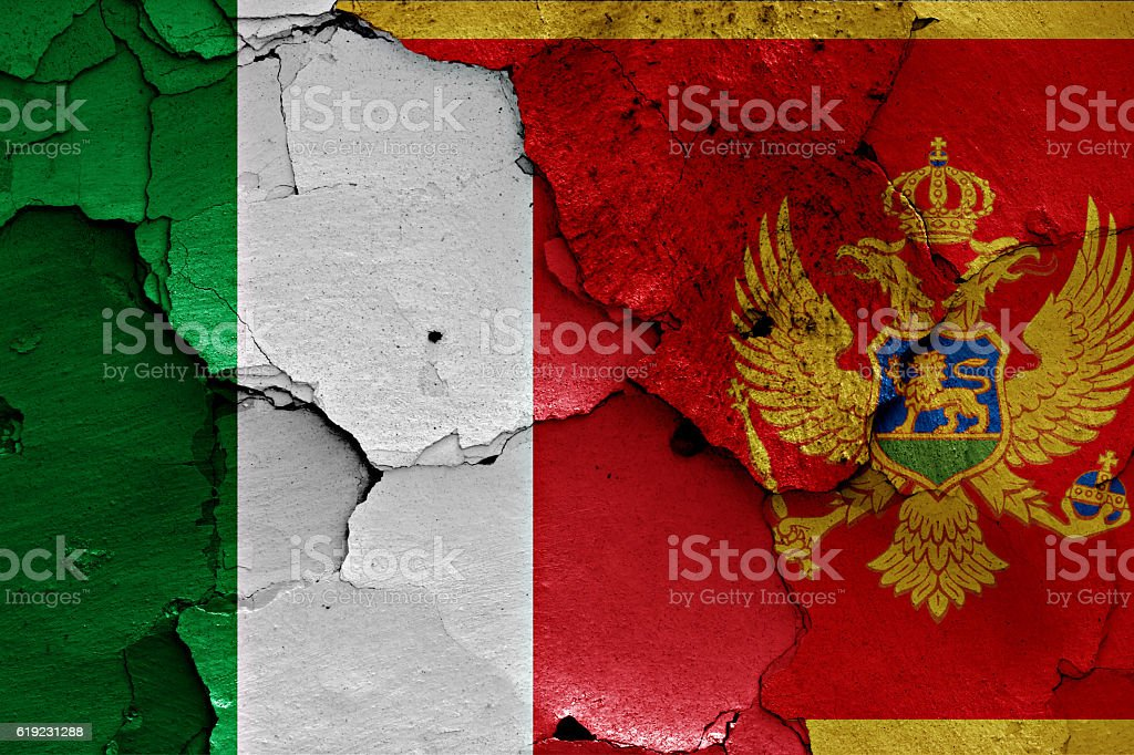 flags of Italy and Montenegro painted on cracked wall stock photo