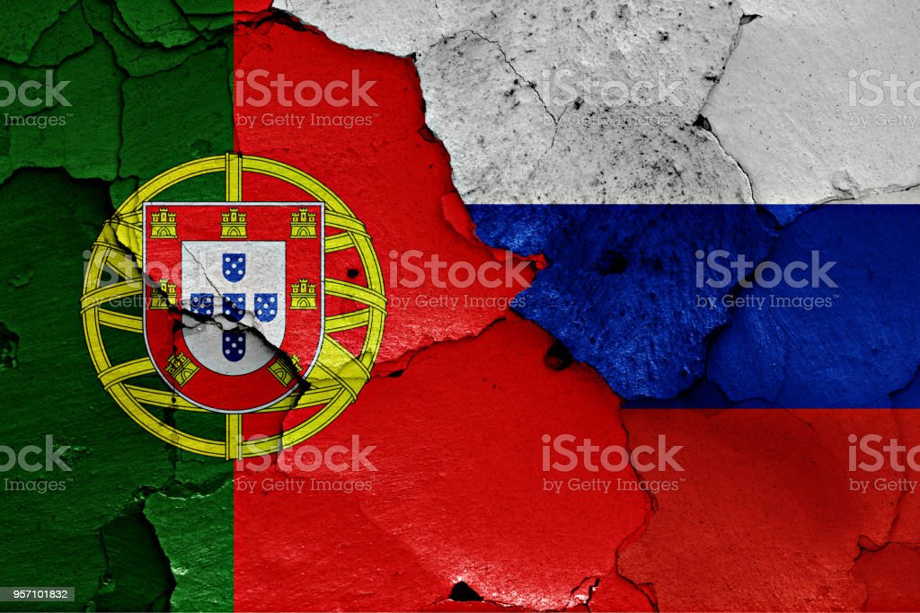 flags of Portugal and Russia painted on cracked wall stock photo