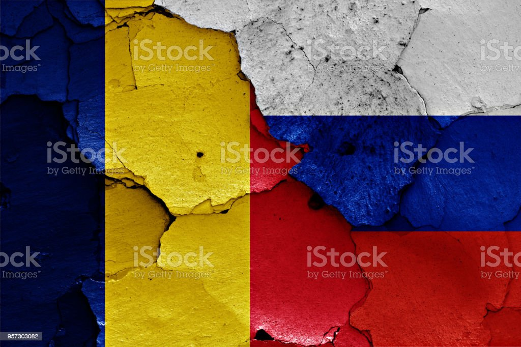 flags of Romania and Russia painted on cracked wall stock photo