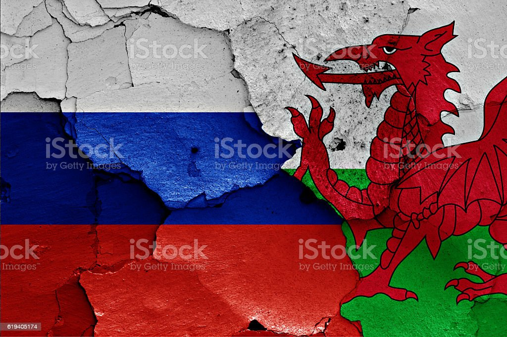 flags of Russia and Wales painted on cracked wall stock photo
