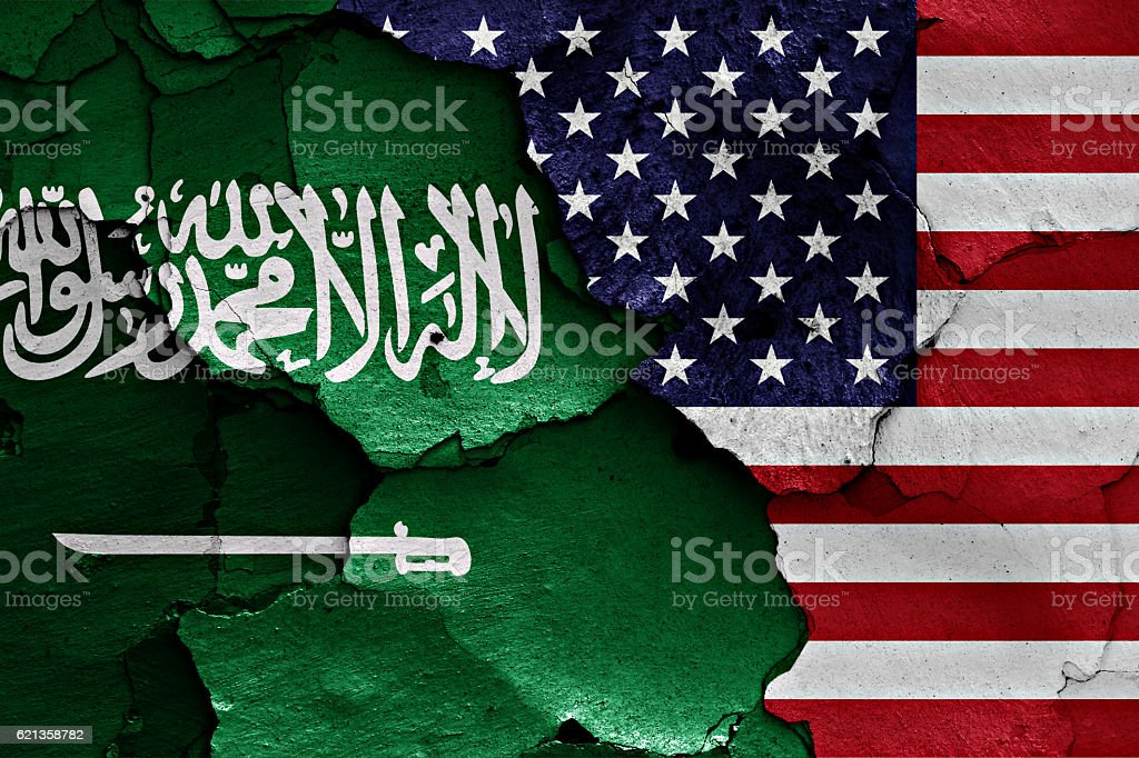 flags of Saudi Arabia and USA painted on cracked wall stock photo