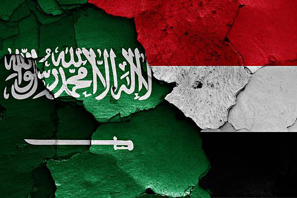 flagi arabia saudyjska i jemen malowane z popękane ściany - saudi national day zdjęcia i obrazy z banku zdjęć