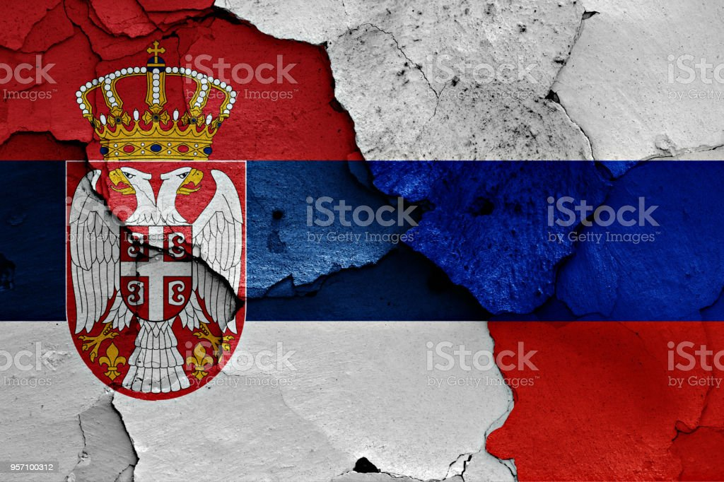 flags of Serbia and Russia painted on cracked wall stock photo