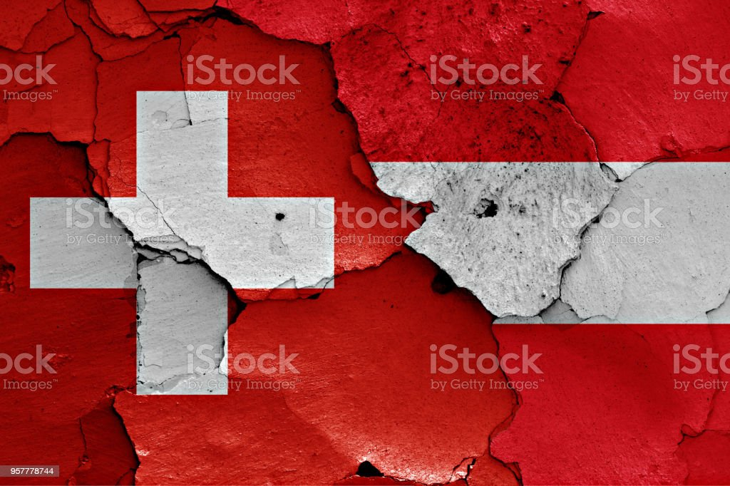 flags of Switzerland and Austria painted on cracked wall stock photo