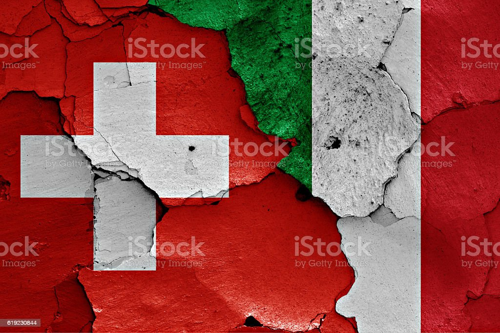 flags of Switzerland and Italiy painted on cracked wall stock photo