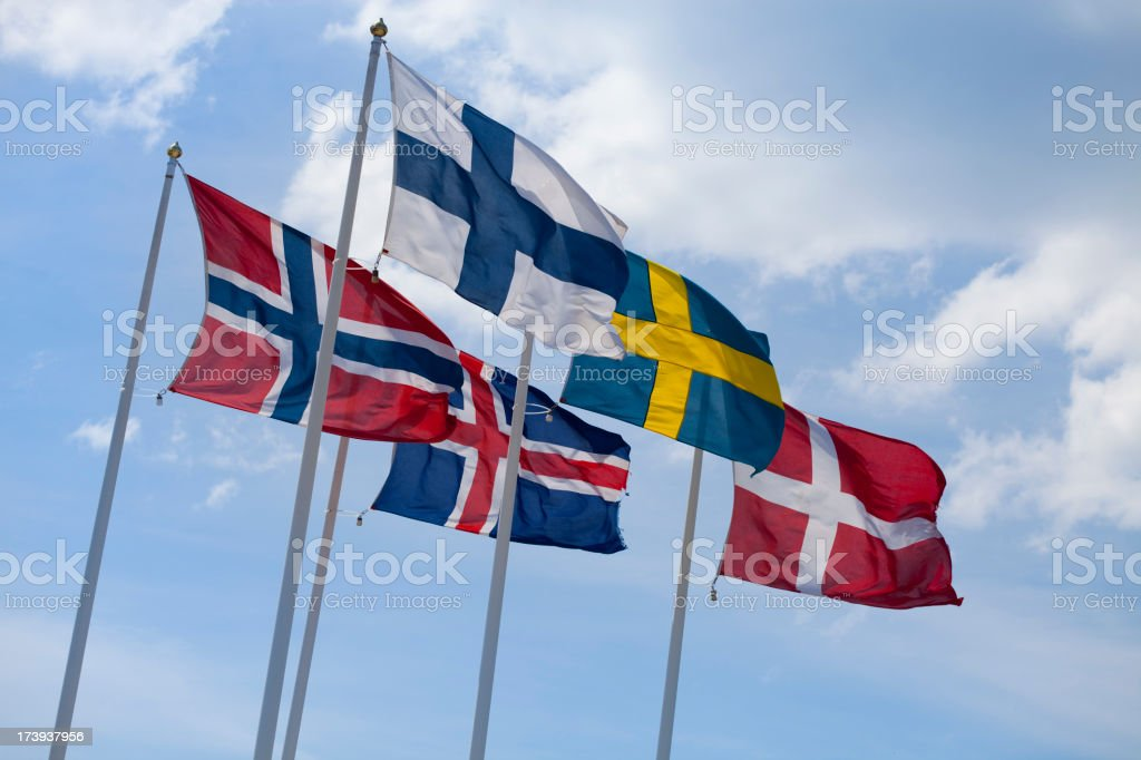 Flags of the Nordic countries on flag poles against blue sky stock photo