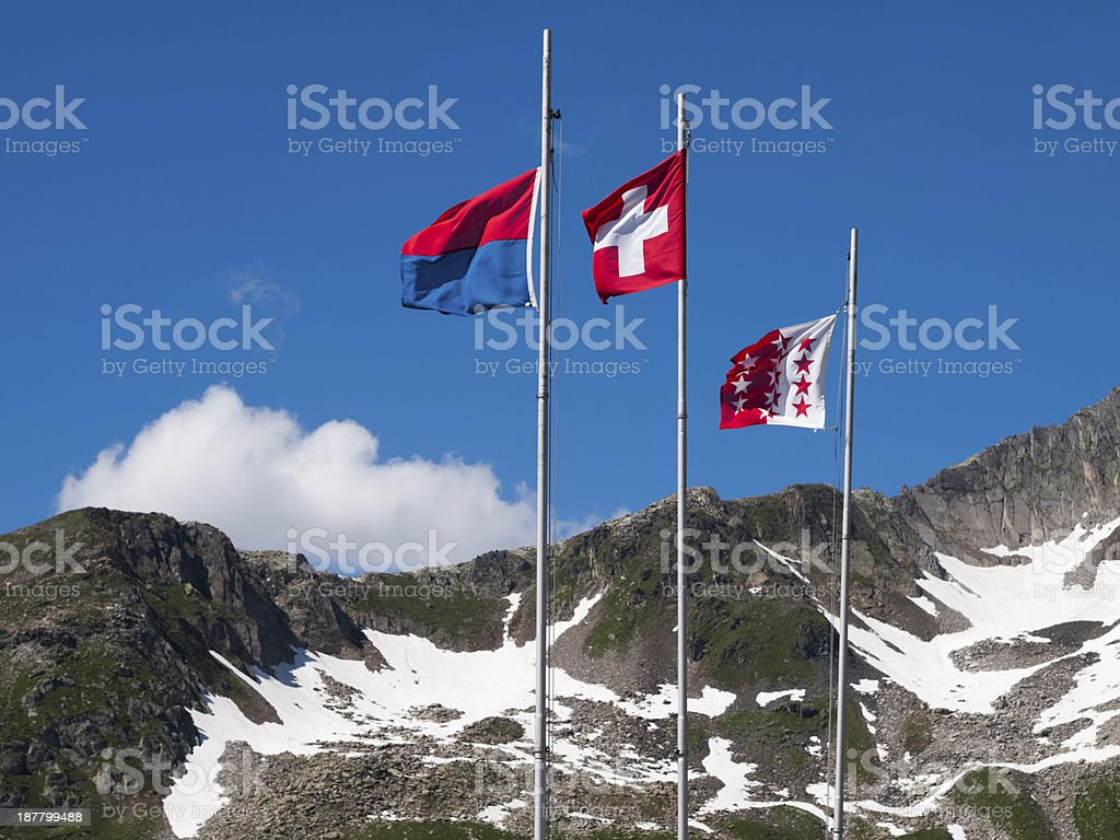 Flags of Ticino, Switzerland and Valais in the wind stock photo