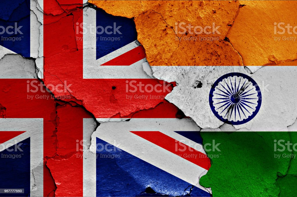 flags of UK and India painted on cracked wall stock photo