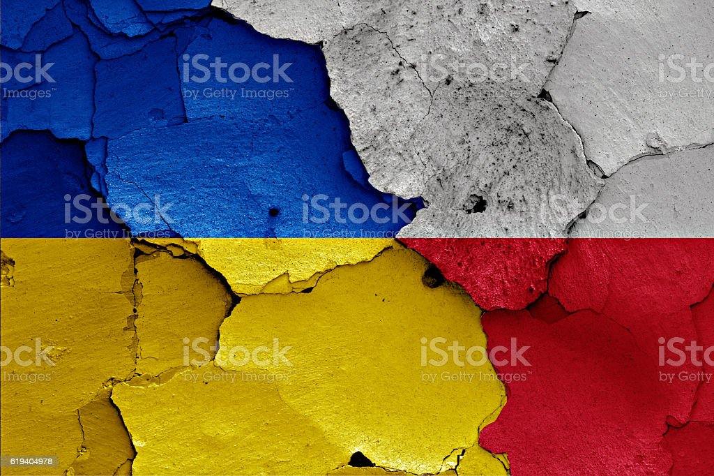 flags of Ukraine and Poland painted on cracked wall stock photo