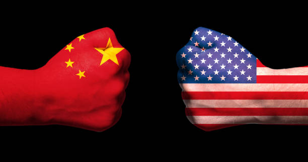 Flags of USA and China on two clenched fists facing each other on black background/usa china trade war concept stock photo