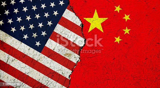 Flags of USA and China painted on cracked wall background