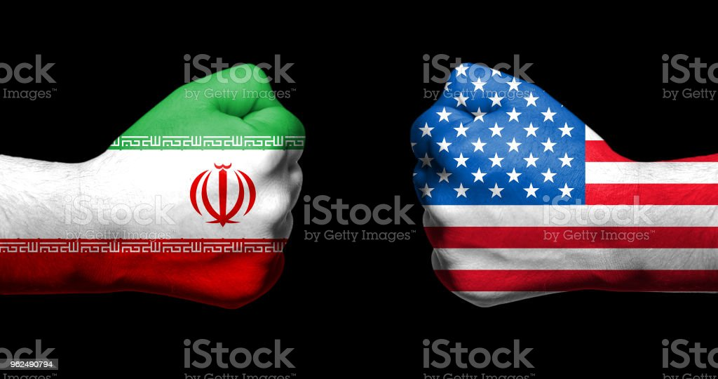 Flags of USA and Iran painted on two clenched fists facing each other on black background/Tensed relationship between USA and Iran concept stock photo