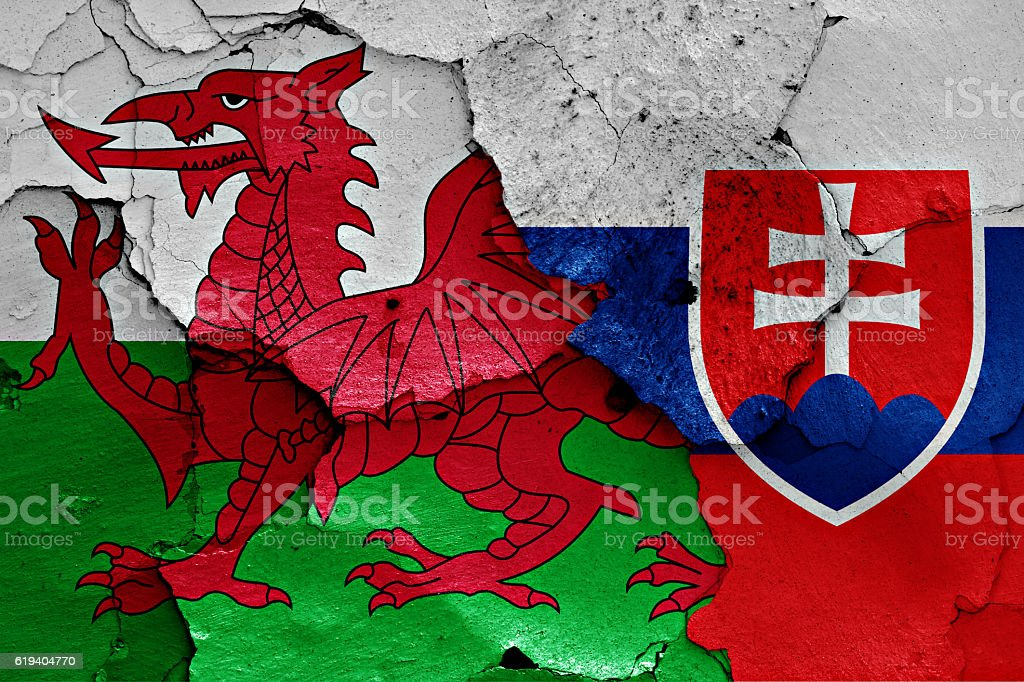 flags of Wales and Slovakia painted on cracked wall stock photo