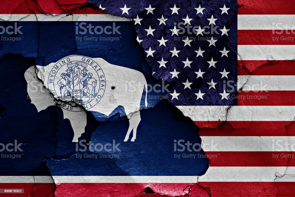 flags of Wyoming and USA painted on cracked wall stock photo