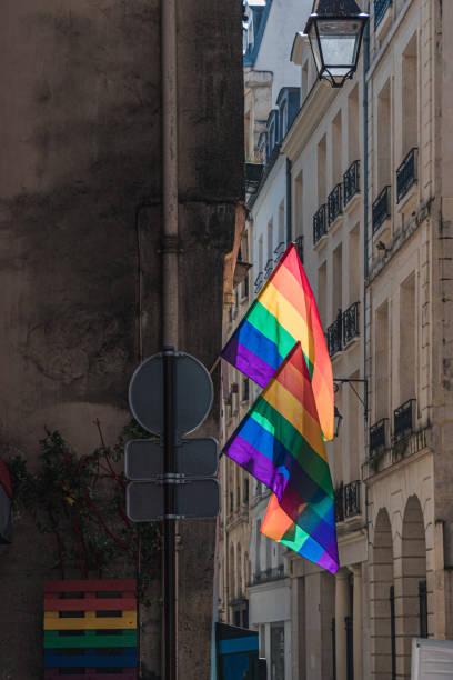 LGBTQ flags on corner of old building in Paris during pride. Transgender Pride flag stock photo