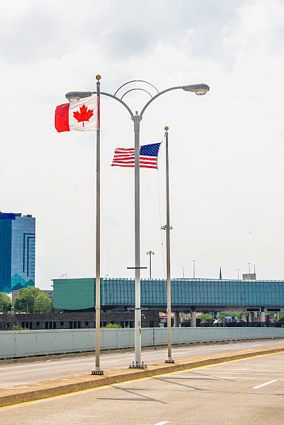 Flags on Rainbow Bridge US Flag and Canada Flag on Rainbow Bridge rainbow bridge ontario stock pictures, royalty-free photos & images