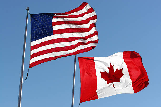 Flags An American & Canadian flag waving in the wind. canada flag photos stock pictures, royalty-free photos & images