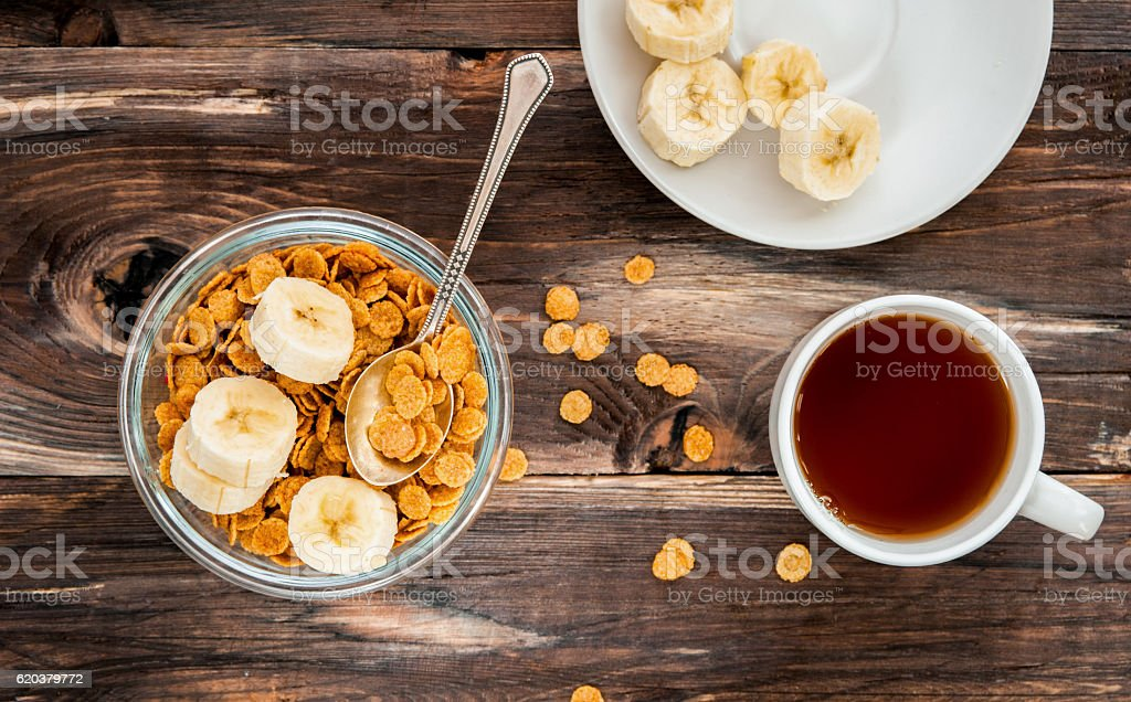 flakes in bowl with banana on wooden background top view zbiór zdjęć royalty-free