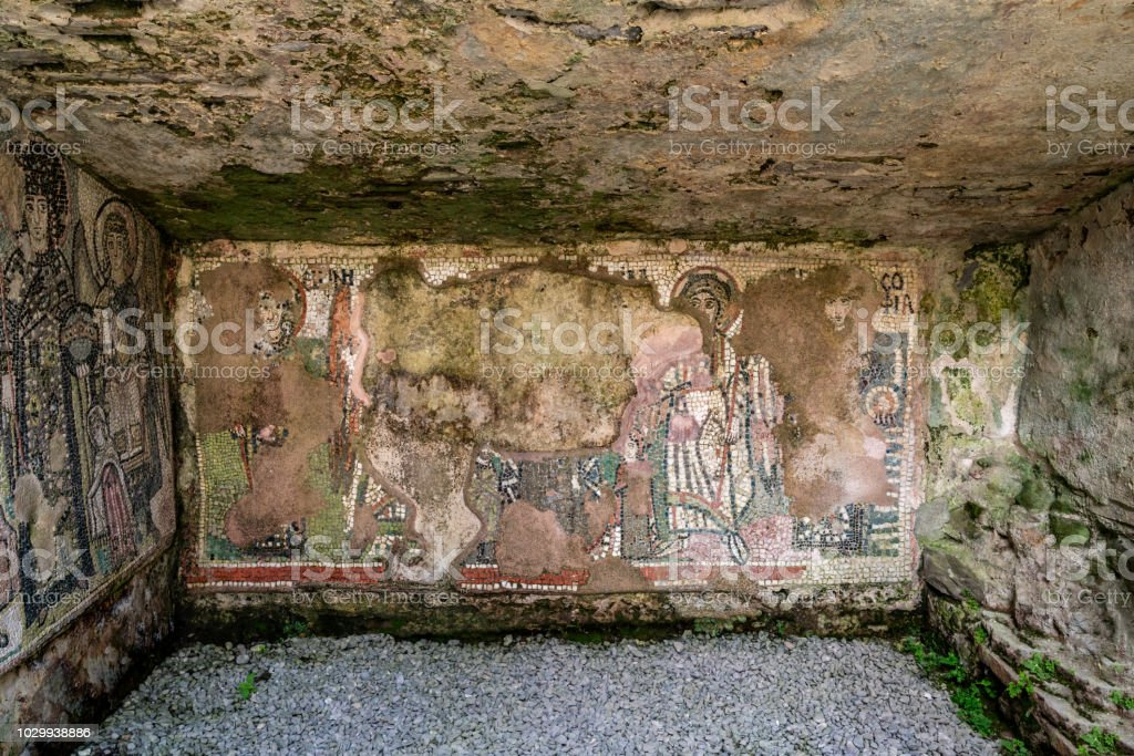 Flaking mosaic figures on a wet ancient roman cave wall. stock photo