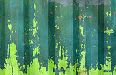 Flaking paint on rusty metal green yellow blue background
