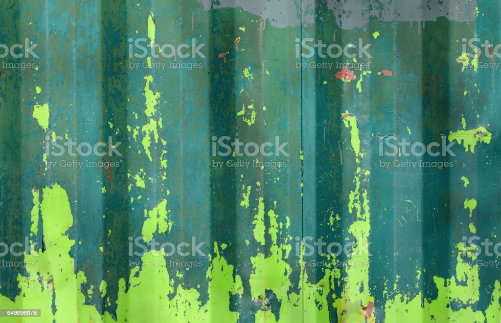 Flaking paint on rusty metal green yellow blue background stock photo