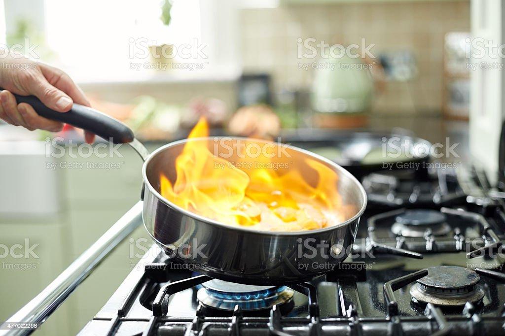 Flambé flames rising in frying pan with mushrooms stock photo