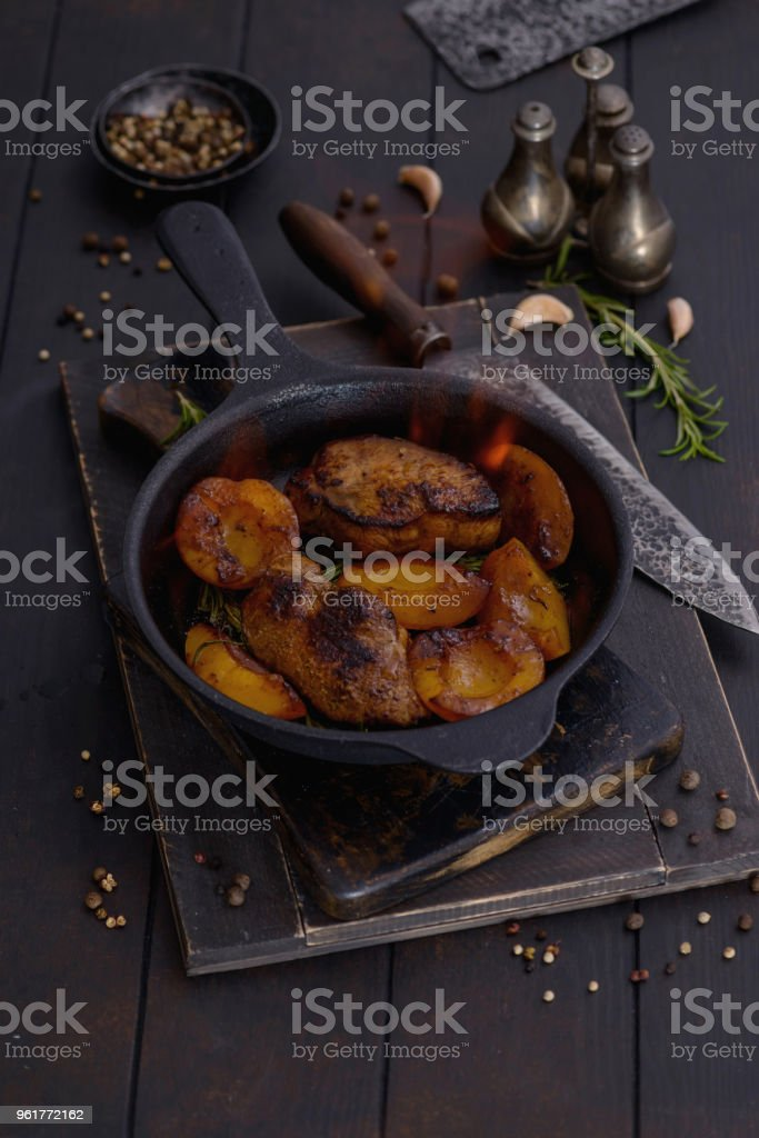 Flambe to pork with peach in pan stock photo