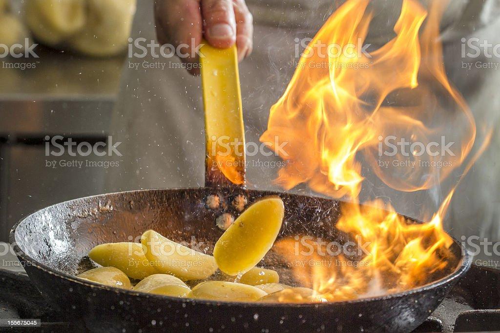 Flambing potatoes stock photo