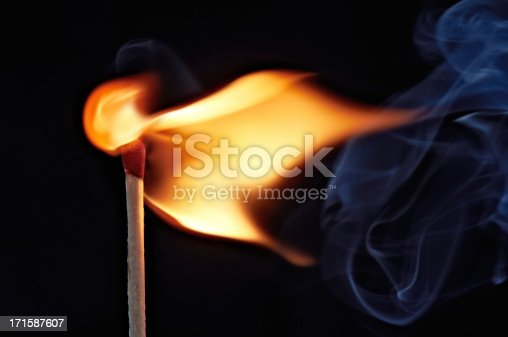 Colorful smoke and flame from a burning match against a black background.