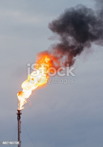 A large flame, and dirty smoke rising from an oil refinery chimney.