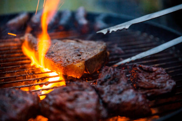 flame grilled steaks being flipped on barbecue with tongs - grill zdjęcia i obrazy z banku zdjęć