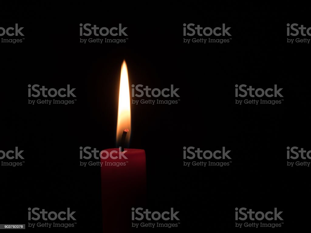 flame of a candlelight in the darkness stock photo