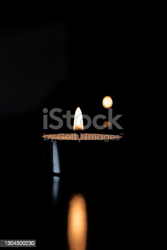 Flame of a small candle in the dark with reflection
