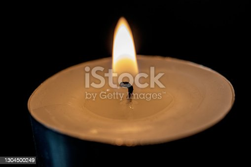Flame of a small candle in the dark close up