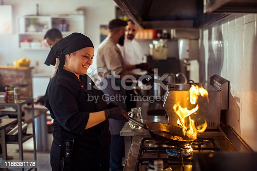 Close up of a chef Flambéing in a restaurant kitchen