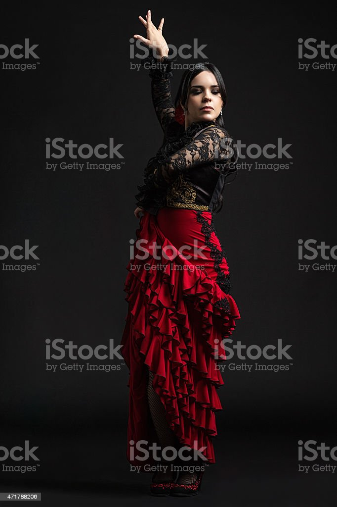 Flamenco dance in a red ruffled skirts against black wall stock photo