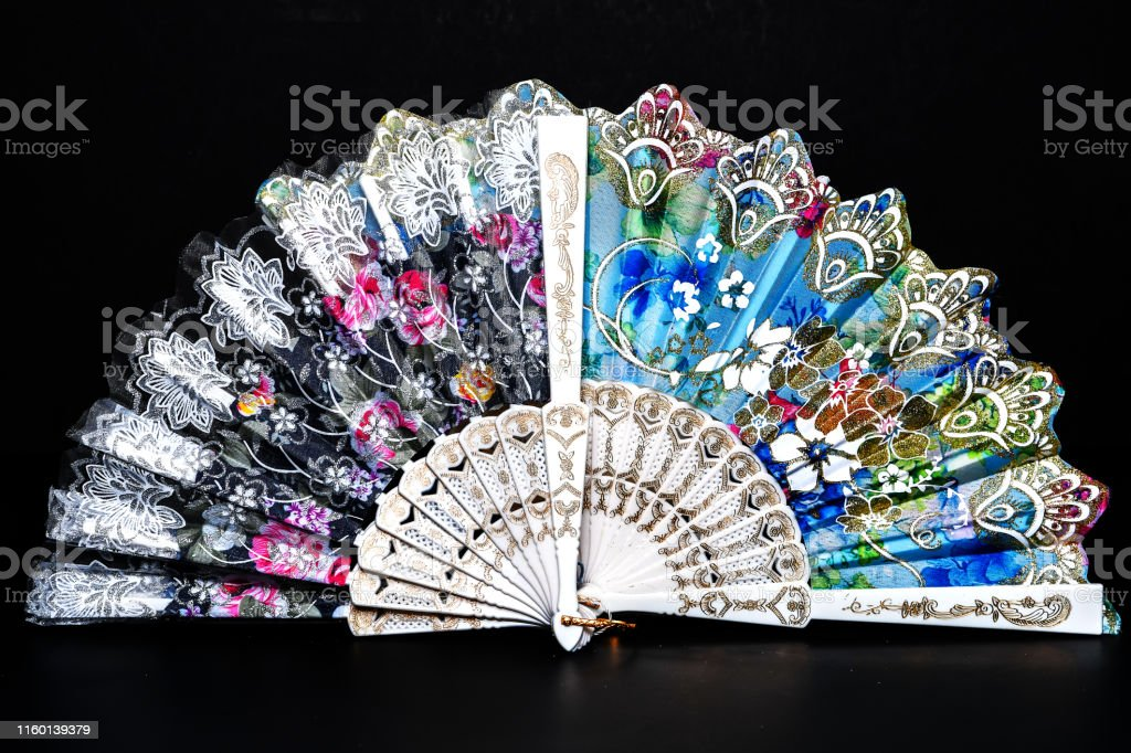 Flamenco hand fan with colorful pattern isolated on black background....