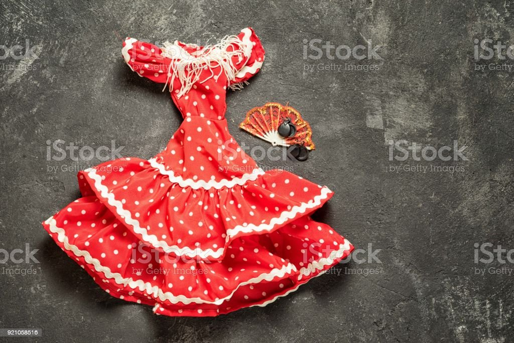 flamenco traditional dress for doll with fan and castanets on a black cement background, top view with copy space stock photo
