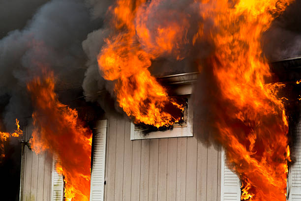 Flames erupting from window in burning home stock photo