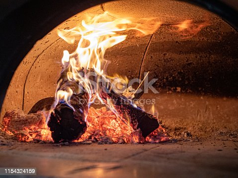 istock Flames, logs, ashes, embers inside wood burning pizza oven 1154324159