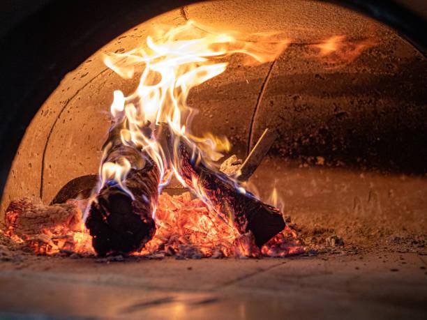 flames, logs, ashes, embers inside wood burning pizza oven - burned oven imagens e fotografias de stock