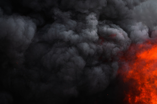 Dangerous red flames of strong fire and dramatic black clouds of smoke covered sky. Natural atmospheric dispersion. Soft, selective focus, motion blur from fire and high temperature from flames.