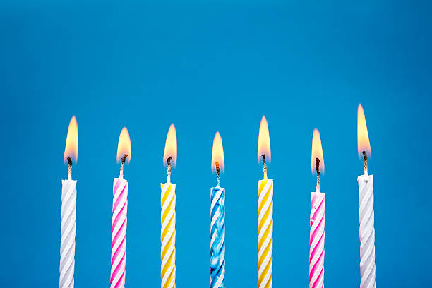 Flaming Birthday Candles on blue background A row of burning birthday candles, on a blue background.. Canon 5D MK III birthday candle stock pictures, royalty-free photos & images