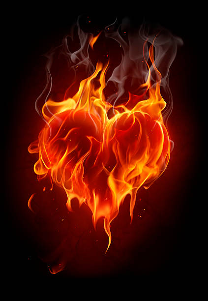 Flaming heart on black background stock photo