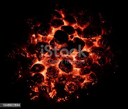 Flaming hot charcoal briquettes in detail. BBQ grill texture, food background