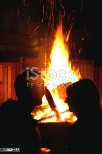 Two people sitting in front of a large campfire